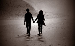 Silhouette of couple walking on a beach. Stock Photos