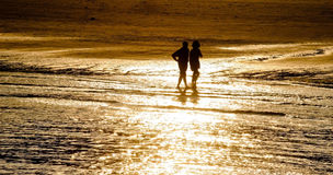 Silhouette of couple walking on beach in sunset Stock Photography