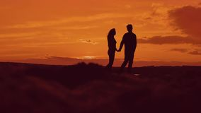 Silhouette of couple walking on beach at sunset holding hands. happy man and girl on seashore in the lights of sunset
