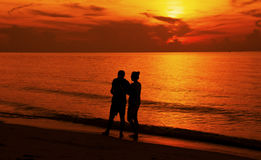 Silhouette of a couple walking on the beach at sunset. Royalty Free Stock Image
