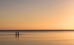 Silhouette Couple walking in the Ocean Sea at Sunset. A silhouette couple walking in the ocean sea at sunset holding hands in love Royalty Free Stock Photos