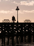 Silhouette of Couple Walking On Pier At Dusk Stock Photography