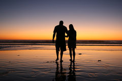 Silhouette of couple walking in sunset. Couple Walks in Sunset in a Silhouette with a glow Stock Image
