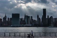 A silhouette of a couple walking on the waterfront in Long Island City royalty free stock image