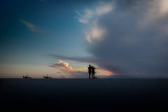 Silhouette of a couple photographing a dramatic sunset. Man and woman silhouette watching beautiful sunset royalty free stock photo