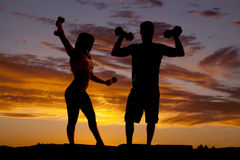 Silhouette couple with weights flex Stock Image