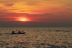 Silhouette of couples are kayaking in the sea at sunset. Kayak in the tropical sea at sunset. Romantic couple travel on summer. Vacation. Adventure activities royalty free stock image