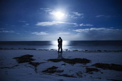 Silhouette couples night at the seaside Stock Photos