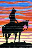 Silhouette of cowboy. Painted slhouette on brick wall of cowboy during sunset Stock Photography