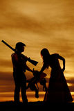 Silhouette of cowboy couple hold saddle and gun Stock Photo