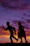 Silhouette of a cowboy with a gun run woman Stock Photos
