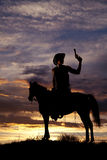 Silhouette of cowboy with gun sitting in saddle on horse Royalty Free Stock Photos