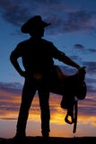 Silhouette of cowboy holding saddle at hip look right Stock Image