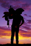 Silhouette of cowboy holding saddle on shoulder. A silhouette of a cowboy in the sunset with a saddle on his shoulder Stock Images