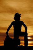 Silhouette of cowboy kneeling by saddle look to side Royalty Free Stock Image