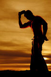 Silhouette cowboy no shirt hat off head Stock Image