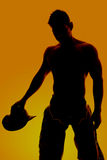 Silhouette cowboy no shirt hold hat down Stock Image