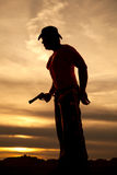 Silhouette cowboy no shirt hold pistol at waist Stock Photography