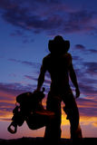Silhouette cowboy no shirt hold saddle look down Royalty Free Stock Images