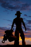 Silhouette cowboy no shirt hold saddle look side Stock Images