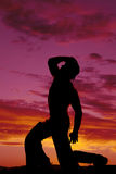 Silhouette cowboy no shirt kneel one knee hand on hat look up Stock Photography