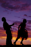Silhouette cowboy with rope around a woman Stock Images