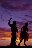 Silhouette cowboy rope woman. A silhouette of a cowboy getting ready to rope his lady Royalty Free Stock Image