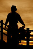 Silhouette cowboy saddle in front of fence. A silhouette of a cowboy holding on to his saddle by a fence Stock Photos