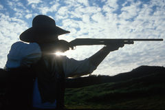Silhouette of cowboy shooting rifle Royalty Free Stock Images