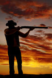 Silhouette of cowboy with shotgun aimed in sunset Royalty Free Stock Photography