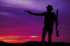 Silhouette of a cowboy shotgun in hand pistol pointed Royalty Free Stock Images
