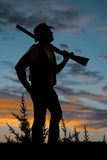 Silhouette of cowboy with shotgun over shoulder sunset Stock Photography