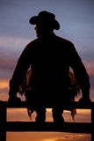 Silhouette of cowboy sitting on fence Royalty Free Stock Photo