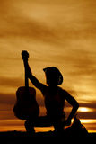 Silhouette of a cowboy sitting on a saddle holding a guitar Stock Photo