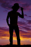 Silhouette of a cowboy in a tank top touching his hat Stock Photography