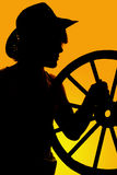 Silhouette of a cowboy and wagon wheel in hand Royalty Free Stock Photo