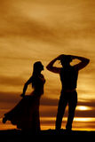 Silhouette cowboy and woman in sunset face each other Stock Photo