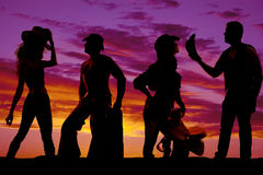 Silhouette of cowboys and cowgirls together in the sunset Stock Image