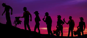 Silhouette of cowboys and cowgirls walking in a line in the suns Stock Photo