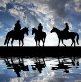 Silhouette cowboys with horses. In the sunset Royalty Free Stock Photos