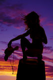 Silhouette cowgirl on barrel hold hat hair blow Stock Photo