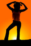 Silhouette of a cowgirl both hands by hat Stock Images