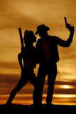 Silhouette of a cowgirl and cowboy together in the sunset Royalty Free Stock Image