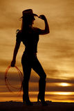 Silhouette cowgirl hold rope touch hat. A silhouette of a woman in her cowgirl hat and holding on to a rope Stock Photography