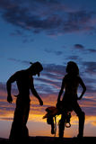 Silhouette of a cowgirl hold saddle hand on hip Stock Photos