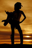 Silhouette of a cowgirl hold saddle on shoulder look to side Stock Photos
