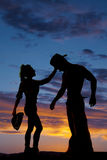 Silhouette of a cowgirl holding her hat reaching up to cowboys h Royalty Free Stock Photo