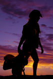 Silhouette of a cowgirl holding a saddle behind her Stock Photos