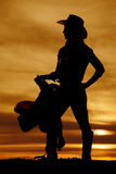 Silhouette of a cowgirl holding saddle on hip Royalty Free Stock Image