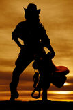 Silhouette of cowgirl holding saddle straight on Royalty Free Stock Images